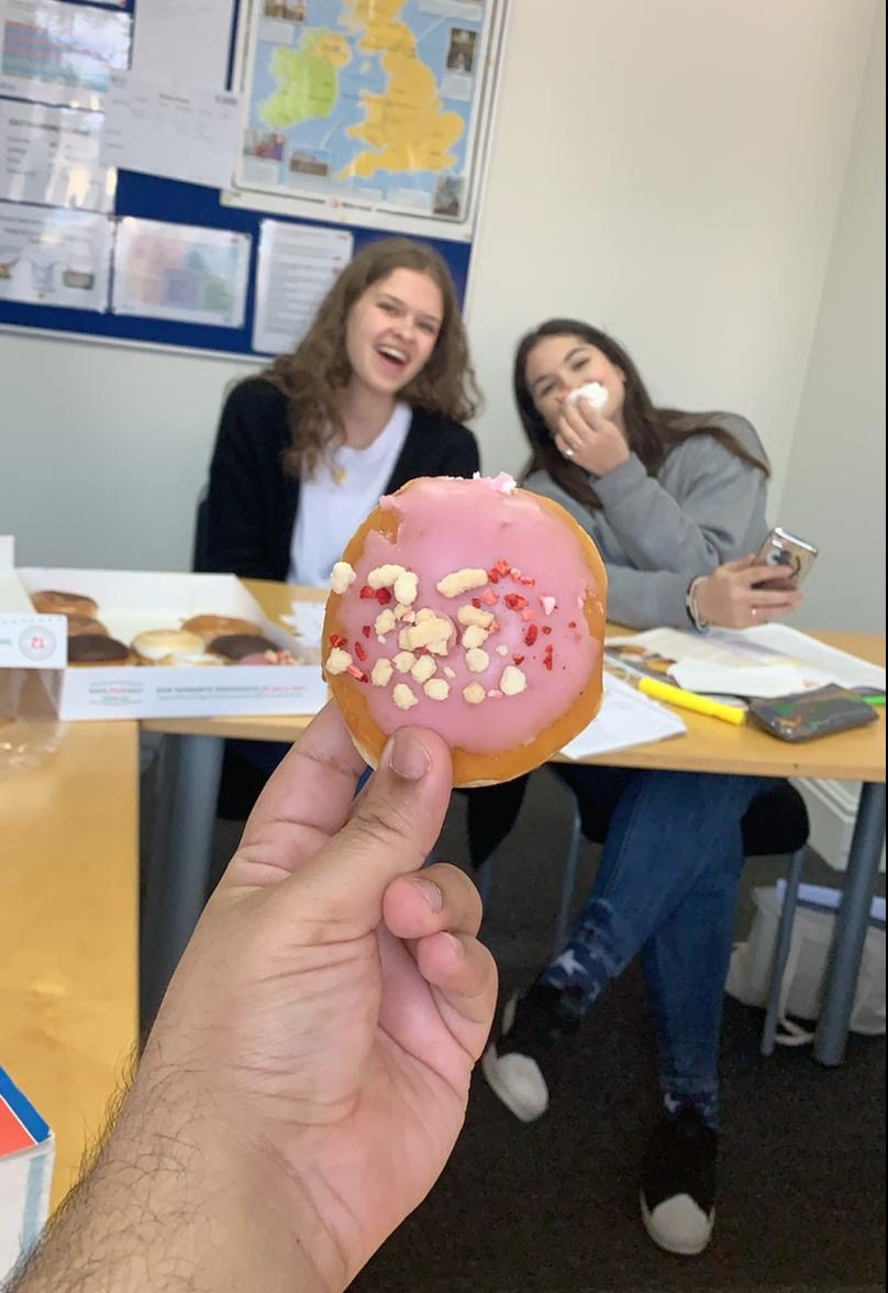 Laura and her friend eating donuts in class